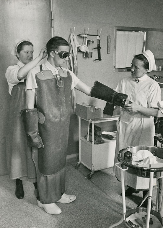 DRK nurses clothe a physician in radiation protection clothing